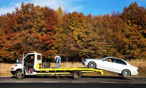 loading scrap car onto tow truck
