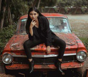 woman sitting on scrap car